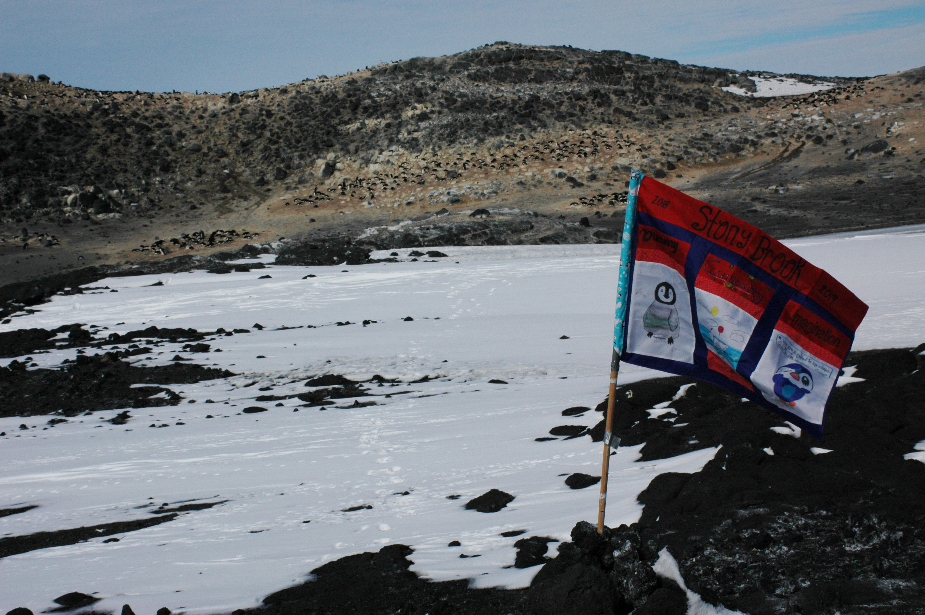 An SB Flag created by 2018 Gr6 students with all of their names flying in Antarctica at a research facility.